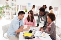 Multietnisk grupp av högskolestudenter som tillsammans studerar Arkivbild