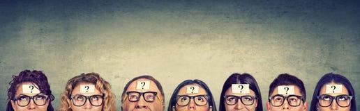Multietnisk grupp av tänkande folk i exponeringsglas med frågefläcken som ser upp Arkivfoto