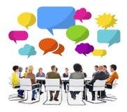 Multietnisk grupp i ett möte med anförandebubblor Royaltyfri Bild