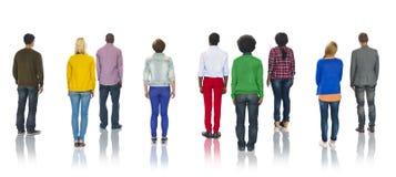 Multietnisk grupp människor som står begrepp för bakre sikt arkivfoto