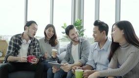 Multietnisk idérik lagmångfald av ungdomargrupperar hållande kaffekoppar för laget och att diskutera idémöte stock video