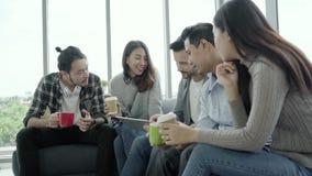 Multietnisk idérik lagmångfald av ungdomargrupperar hållande kaffekoppar för laget och att diskutera idémöte arkivfilmer