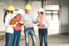 Multietnisk olik grupp av teknikerer eller affärspartners på konstruktionsplatsen som tillsammans arbetar på ritning för byggnads arkivfoto