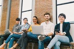 Multietnisk olik grupp av ungt och vuxet folk som tillsammans använder smartphonen, anteckningsbokdator, digital minnestavla royaltyfri fotografi