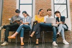 Multietnisk olik grupp av ungt och vuxet folk som tillsammans använder smartphonen, bärbar datordator, digital minnestavla arkivfoton
