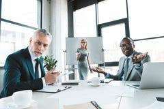 multietniska affärskollegor som ser kameran, medan ha konversation fotografering för bildbyråer