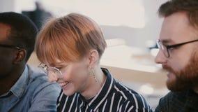 Multietniska affärspartners på möte, erbjudande arbetsidéer för ung härlig kvinnlig chef bak kontorslagtabellen arkivfilmer