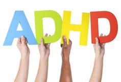 Multietniska armar lyftt hållande ADHD royaltyfria foton