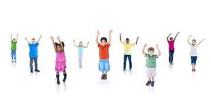 Multietniska barn med deras lyftta armar Royaltyfri Bild