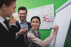 multietniska businesspeople som arbetar med whiteboard och uppgift, stiger ombord med klibbiga anmärkningar arkivbild