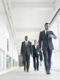 Multietniska Businesspeople som i regeringsställning går korridoren Arkivfoton