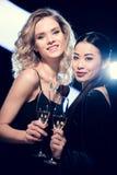 Multietniska flickor för glamour som rostar med champagneexponeringsglas och ser kameran på partiet Royaltyfria Bilder