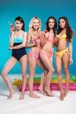 Multietniska flickor i swimwear som poserar och rymmer flaskor med coctailar Arkivfoto