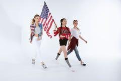 Multietniska flickor som går med amerikanska flaggan och firar 4th juli Royaltyfri Foto