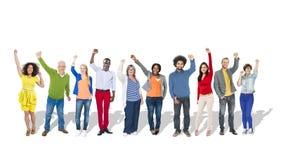 Multietniska lyftta grupp människorarmar Arkivbild