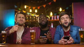 Multietniska manliga vänner som håller ögonen på fotbollsmatchen i bar, rubbning med att förlora för lag lager videofilmer