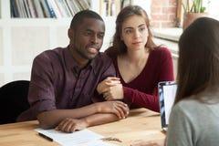 Multietniska par som betraktar, intecknar investeringfastighet p Arkivfoton