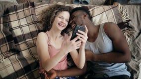 Multietniska par som ligger på säng och använder smartphonen Lyckliga man och kvinna tillsammans Man och kvinnligt skratta och at Arkivfoton