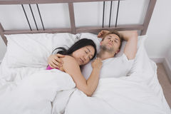 Multietniska par som sover i säng Arkivbild