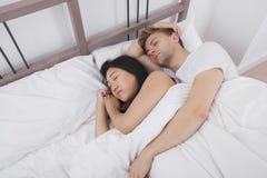 Multietniska par som vilar i säng Arkivbilder