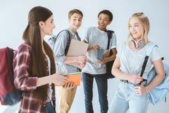 multietniska studenter med ryggsäckar som har konversation tillsammans royaltyfri fotografi