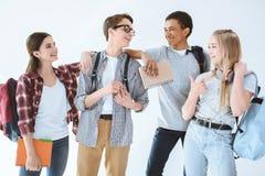 multietniska studenter med ryggsäckar som har konversation tillsammans royaltyfri bild