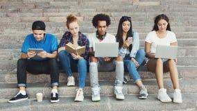 Multietniska tonåriga vänner som studerar och knyter kontakt som är utomhus- arkivfoton