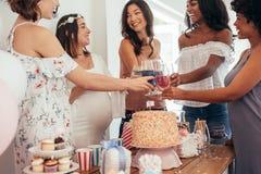 Multietniska vänner som har ett rostat bröd på baby shower Royaltyfri Bild