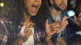 Multietniska vänner som korsar fingrar för stöttande sportlag för bra lycka i bar arkivfilmer