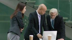 Multietniskt affärsfolk som i regeringsställning möter lager videofilmer