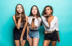 Multietniskt av tre unga gulliga flickavänner som blåser kyssar som står isolerade över blå bakgrund royaltyfri bild