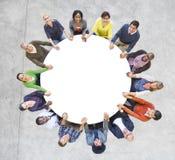 Multietniskt folk som bildar händer för ett cirkelinnehav Royaltyfria Bilder