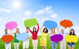 Multietniskt folk som rymmer den färgrika anförandebubblan Arkivfoton