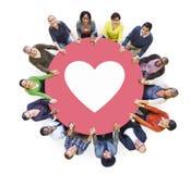 Multietniskt folk som rymmer händer med hjärtasymbol royaltyfri fotografi
