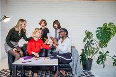 Multietniskt kvinnligt lag som applåderar under affärsseminarium i konferenskorridor royaltyfria bilder