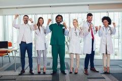 Multietniskt lag av doktorer i sjukhuset som ser kameran och att se lyckligt royaltyfri fotografi