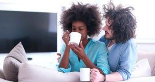 Multietniskt parsammanträde på hemmastadd dricka coffe för soffa royaltyfria bilder