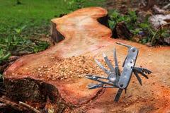 Multifunction knife stuck on the tree stump. Royalty Free Stock Photo