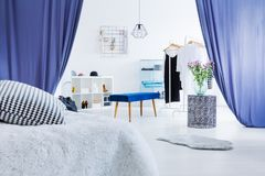 Multifunctional bedroom with blue curtains. Pillow on bed in multifunctional bedroom with blue curtains in entrance to dressing room Stock Photo