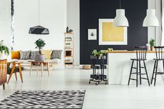 Multifunctional chic living room. Geometric carpet in multifunctional chic living room with rustic bar stools at kitchenette royalty free stock photography