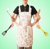 The multifunctional cook. The multifunctional woman cook with lots of hands on the kitchen tools royalty free stock photography