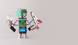 Multifunctional electrician robot with light bulbs and pliers in four hands. Colorful circuit board toy character holds stock photos