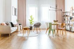 Multifunctional living room interior. Wooden table with book on round rug near sofa in multifunctional living room interior with green chair at dining table royalty free stock image