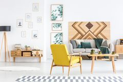 Multifunctional living room interior. Yellow armchair next to wooden table in multifunctional living room interior with gallery and beige sofa stock image