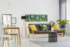 Multifunctional living room interior. Yellow cushions on black sofa near lamp and chairs at table in multifunctional living room interior with green poster royalty free stock images