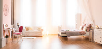 Multifunctional room with double bed. Sofa and dressing table, panorama royalty free stock photography