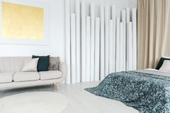 Multifunctional room with gold painting. Patterned blanket on bed and gold painting on the wall above grey sofa in multifunctional room with tube decoration royalty free stock images