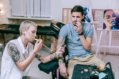 Multifunctional tattoo artist working with tattoo and smoking Electronic Cigarette. Treating with cookies. Multifunctional tattoo artist working with tattoo and stock photography