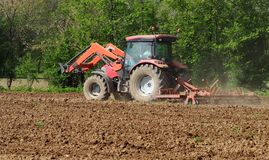 Multifunctional tractor, with front loader and land plowing machine, plows the  field in spring.  royalty free stock photos