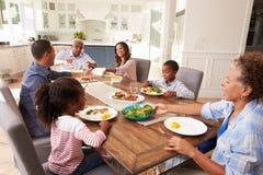 Multigeneratie zwarte familie die een maaltijd in de keuken dienen stock fotografie